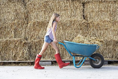 Girl walking with wheelbarrow on horse farm - FSF00794
