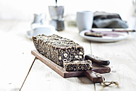 Home-baked wholemeal gluten-ree bread with nuts and seeds on wooden board - SBDF03154