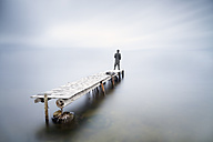 Back view of man standing on jetty watching looking at distance - XCF00138