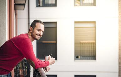 Portrait of smiling man standing on balcony with coffee mug - EPF00329
