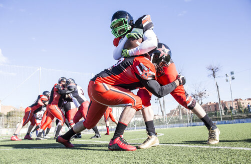 American football player being tackled by opponent player during a match - ABZF01902