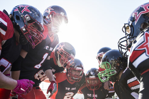 American football players talking and cheering in a circle before a game - ABZF01920