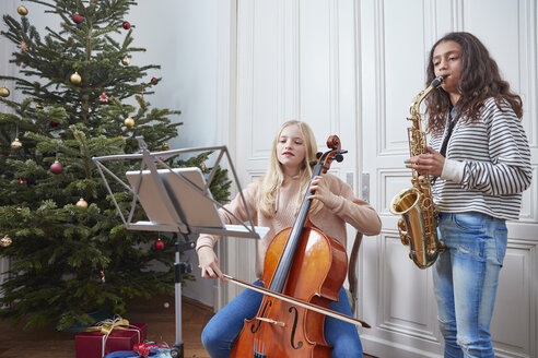 Two girls playing cello and saxophone at Christmas tree - RHF01803