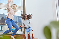 Two enthusiastic girls jumping and dancing at home - RHF01812