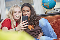 Two girls on couch sharing smartphone - RHF01818