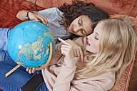 Two girls lying on couch pointing at globe - RHF01821