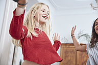 Two happy girls dancing at home - RHF01824