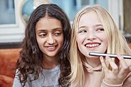 Two happy girls using smartphone - RHF01836