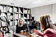 Two businesswomen talking at desk in office - JRFF01182