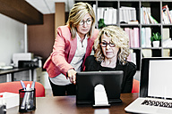 Two businesswomen using laptop at desk in office - JRFF01191