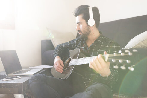 Young man at home playing guitar and wearing headphones connected to laptop - FMOF00156