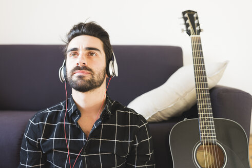 Young man at home wearing headphones next to guitar - FMOF00159