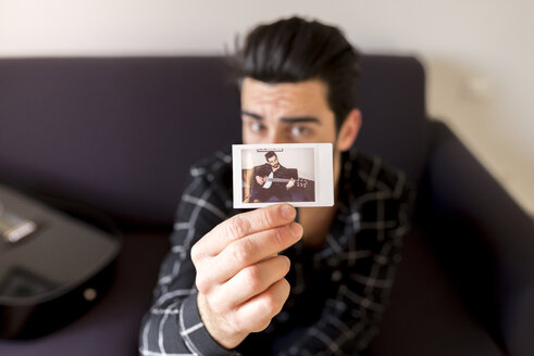 Man showing photography of himself playing guitar - FMOF00174