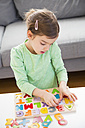 Little girl learning alphabet with wooden letters at home - LVF05870