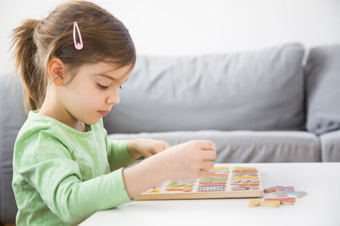 Little girl learning alphabet with wooden letters at home - LVF05873