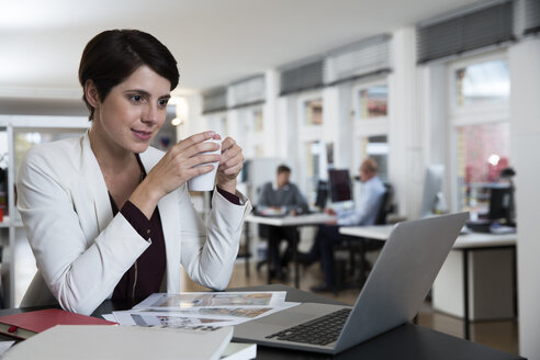 Woman using laptop in office with colleagues in background - FKF02132