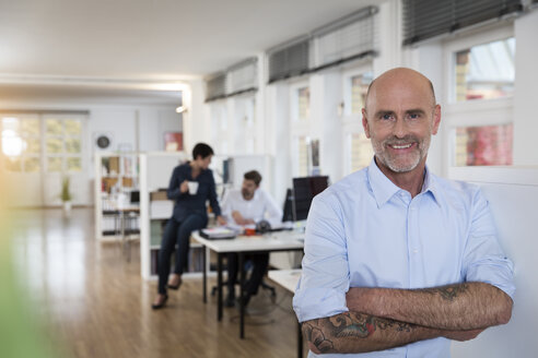 Portrait of confident man in office with colleagues in background - FKF02135