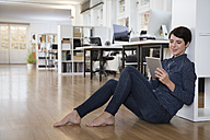 Woman sitting on floor in office using tablet - FKF02138
