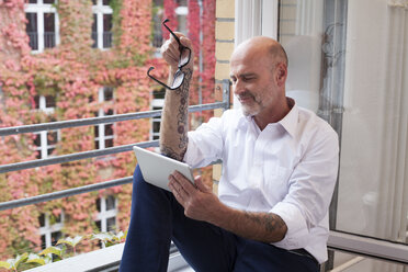 Businessman on cell phone at the window - FKF02147