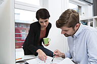 Colleagues working together at desk in office - FKF02150