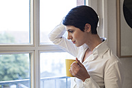 Woman holding cup of coffee looking out of window - FKF02153