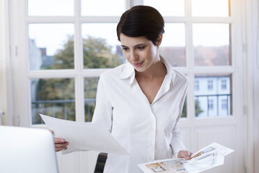 Smiling woman in office looking at papers - FKF02156