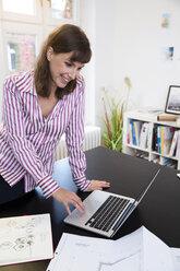 Happy woman using laptop in office - FKF02171