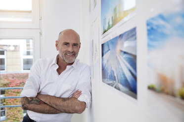 Portrait of smiling tattooed businessman in office - FKF02186