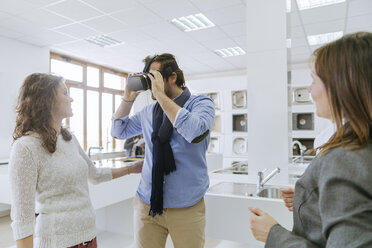 Customers consulting saleswoman in shop for kitchen sinks - ZEDF00512