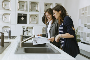 Customers consulting saleswoman in shop for kitchen sinks - ZEDF00515
