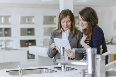 Customers consulting saleswoman in shop for kitchen sinks - ZEDF00518