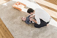 Father changing diapers and playing with his baby son - UUF09869