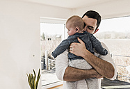 Father holding and hugging his baby son, standing in comfortable home - UUF09872