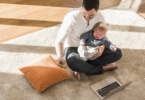 Father sitting cross-legged with baby son on lap, using laptop and smart phone - UUF09884