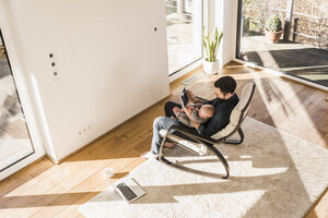 Father sitting in arm chair with baby son on lap, using mobile devices - UUF09893