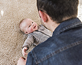 Father cuddling laughing baby son - UUF09899