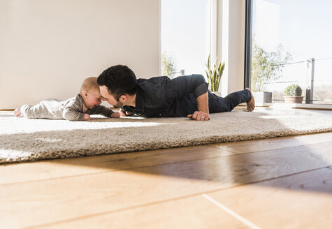 Father and baby son playing crawling on carpet - UUF09902
