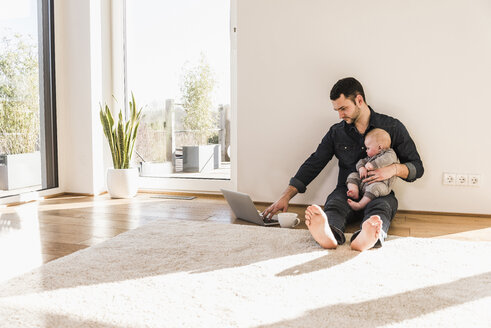 Father with baby son using laptop sitting on floor - UUF09905