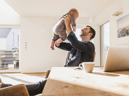 Father sitting at home playing with baby son - UUF09908