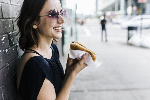 Smiling woman with Hot Dog leaning against wall - GIOF01867