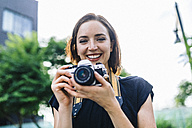 Portrait of smiling woman with camera - GIOF01876
