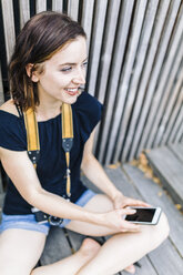Smiling woman with camera and smartphone in summer - GIOF01882