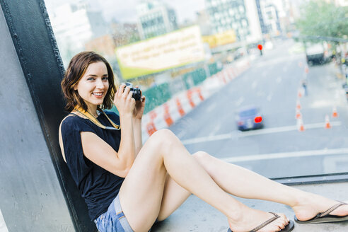 USA, New York City, smiling woman with camera on the High Line in Manhattan - GIOF01885