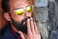 Portrait of man wearing mirrored sunglasses smoking cigarillo - SIPF01404