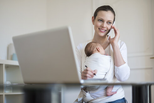 Mother with baby girl in sling working from home - DIGF01510