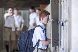 Student opening locker with group of high school students in background - ZEF12797