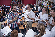 Drama teacher leading students holding booklets - ZEF12812