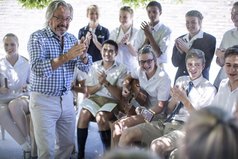 Happy teacher and students having music lessons outside - ZEF12815