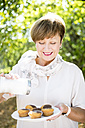 Senior woman sprinkling icing sugar on plate of muffins outdoors - WESTF22670