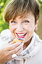 Portrait of smiling senior woman eating a muffin outdoors - WESTF22673